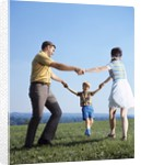 1970s Family Mother Father Boy Playing Ring Around Roses Holding Hands by Corbis