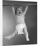 1960s Baby Hanging From Rod With Frightened Expression On Verge Of Tears by Corbis