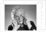 1950s Portrait Of Smiling Old Lady Holding Her Antique Wire Frame Glasses by Corbis