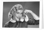 1950s 1960s Smiling Blond Woman Communicating That She Is Mother To Be By Holding Up A Pair Of Baby Shoes Looking At Camera by Corbis