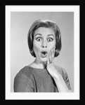 1960s Portrait Woman With Hand On Cheek Looking At Camera With Shocked Expression by Corbis