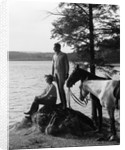 1930s Man Standing On Rock Lakeside Holding Reins Of Two Horses With Woman Seated Beside Looking Off To Side by Corbis