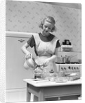 1930s Woman In Kitchen Wearing Apron Making Breakfast Pouring Water Into Coffee Pot by Corbis