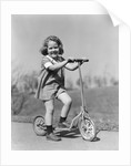 1930s Smiling Girl Playing On Scooter On Sidewalk Looking At Camera by Corbis