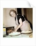Grandma cooks in the kitchen, ca. 1952 by Corbis