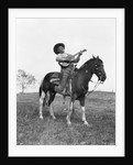 1920s cowboy on horse singing and playing guitar by Corbis