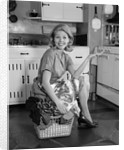 1960s smiling housewife sitting on full laundry basket by Corbis