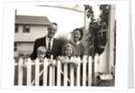 1950s family of four behind picket fence by Corbis