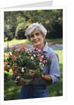 Smiling senior woman holding garden flowers by Corbis