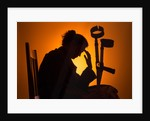 Woman seated with crutches by Corbis