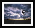 Windmill Silhouette Under Broken Clouds by Corbis