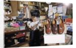Boy Holding Shotgun in Sporting Goods Store by Corbis