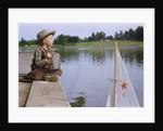 Boy Sitting by Lake in Cowboy Hat by Corbis