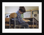 Schoolchild Placing Books in Desk by Corbis