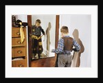 Boy Trying on Cowboy Duds by Corbis