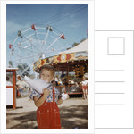 Boy Eating Cotton Candy at Fair by Corbis