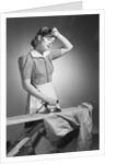 Woman Hard at Work Ironing by Corbis
