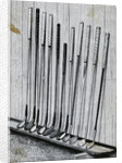 Variety Of Golf Clubs Lean Against Wall by Corbis