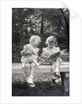 Two Little Girls Sitting On A Bench by Corbis