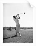 Woman Swinging Golf Club by Corbis