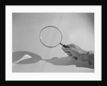 Hand Holding a Magnifying Glass by Corbis