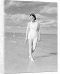 Woman Casually Strolling Along the Beach by Corbis