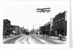 Biplane Over a Small Town by Corbis