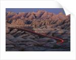 Car Traveling Through Badlands National Park by Corbis