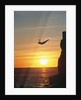Cliff Diver Above Setting Sun by Corbis