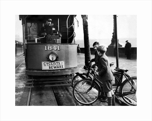 Boys on bicycles cross in front of a tram by Associated Newspapers