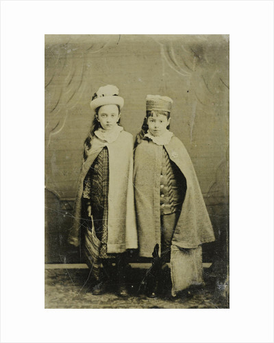 Portrait of two girls with hats and capes, standing in a studio setting by Anonymous