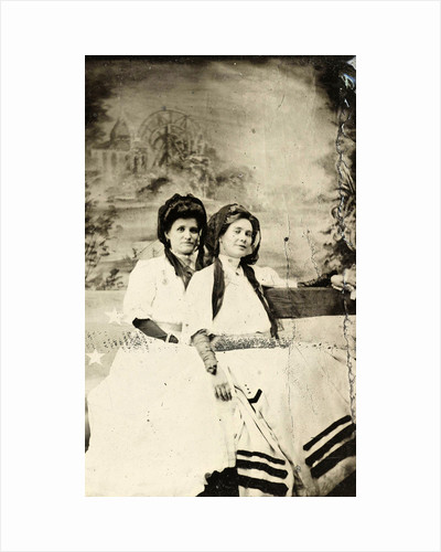 Portrait of two women sitting on a bench in front of a painted backdrop (chapel or church (?) In a lake), in the left part of the American flag by Anonymous