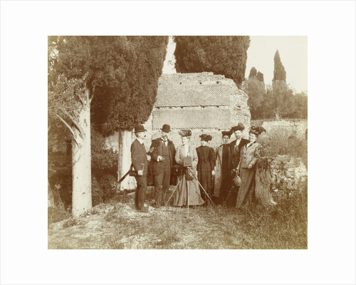 Group portrait of five women (one of whom is behind a camera) and two men for a ruin in Italy or France by Anonymous