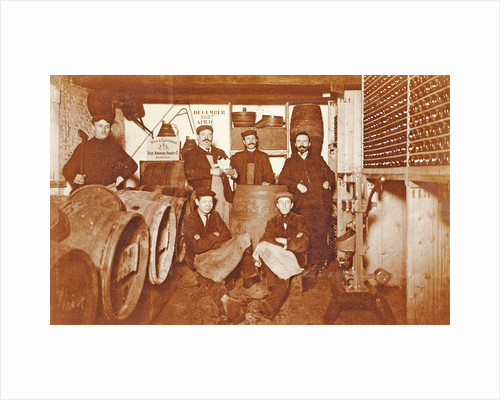 Group portrait of a brewer and servants between barrels and bottles by Anonymous