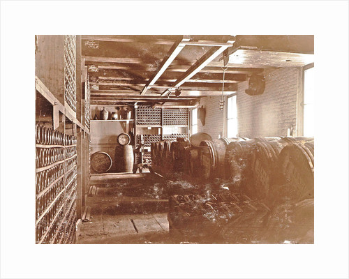 Interior of a brewery: wooden barrels and bottles on shelves by Anonymous