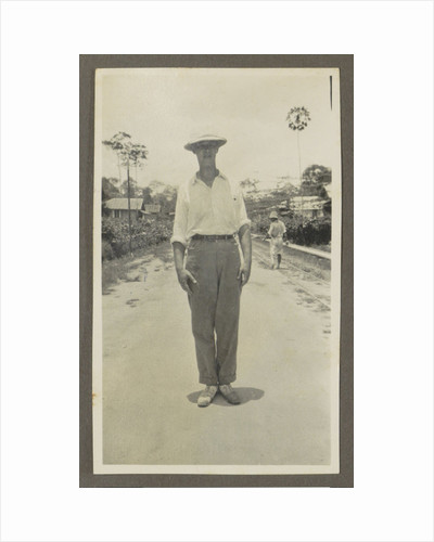 Man wearing a pith helmet posing on a road by Anonymous