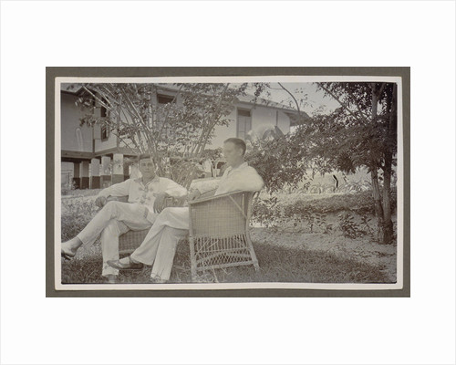 Two men in white clothes sitting in wicker chairs in a garden by Anonymous