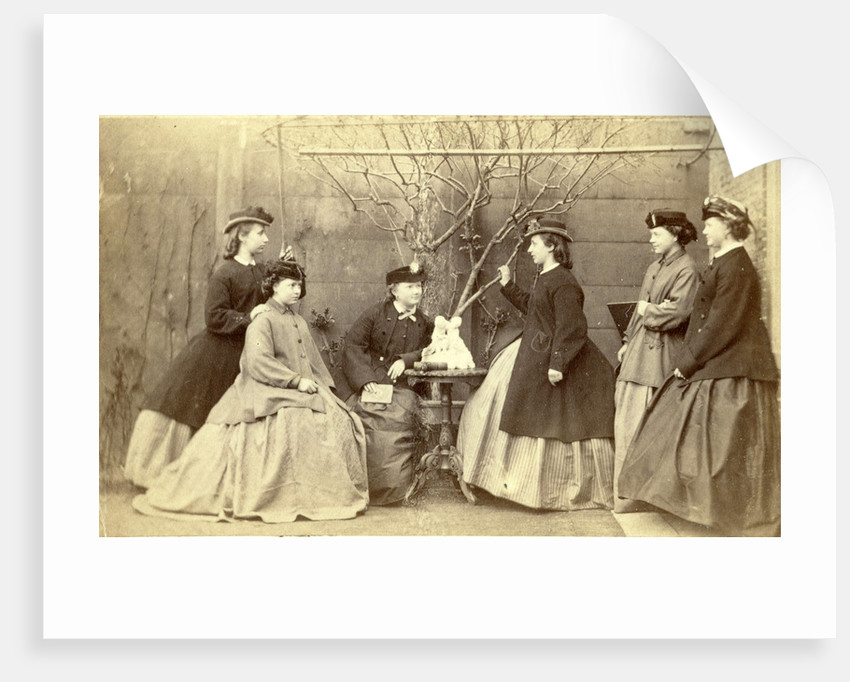 Group portrait of six young women in garden round table with sculpture, hats and coats by L. de Koningh