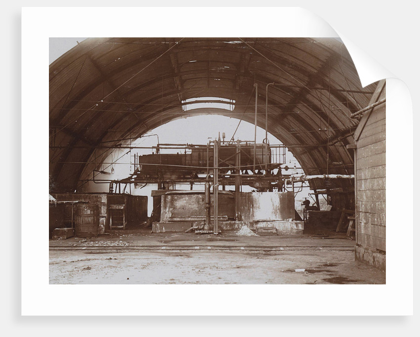 Interior of a half-round factory with a machine and pipe lines by Anonymous