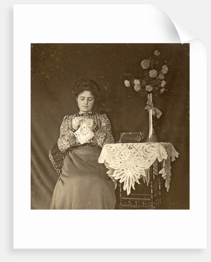 Female working at a table with tablecloth and flowers by Anonymous