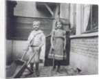 Two children, with wheelbarrow and shovel by Anonymous