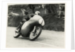 Bob McIntyre, TT (Tourist Trophy) rider, riding 499cc Norton (number 1) over the Mountain by T.M. Badger