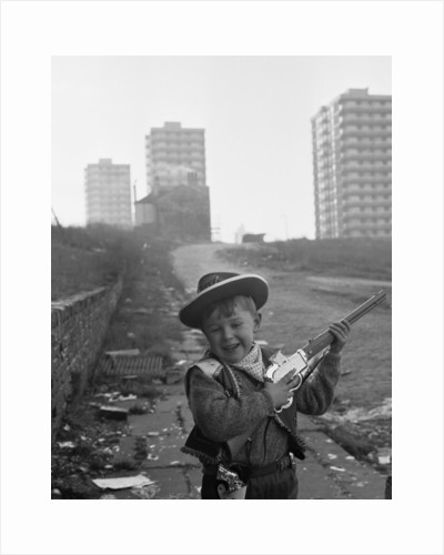 Young boy playing cowboys in Collyhurst by Dennis Hussey