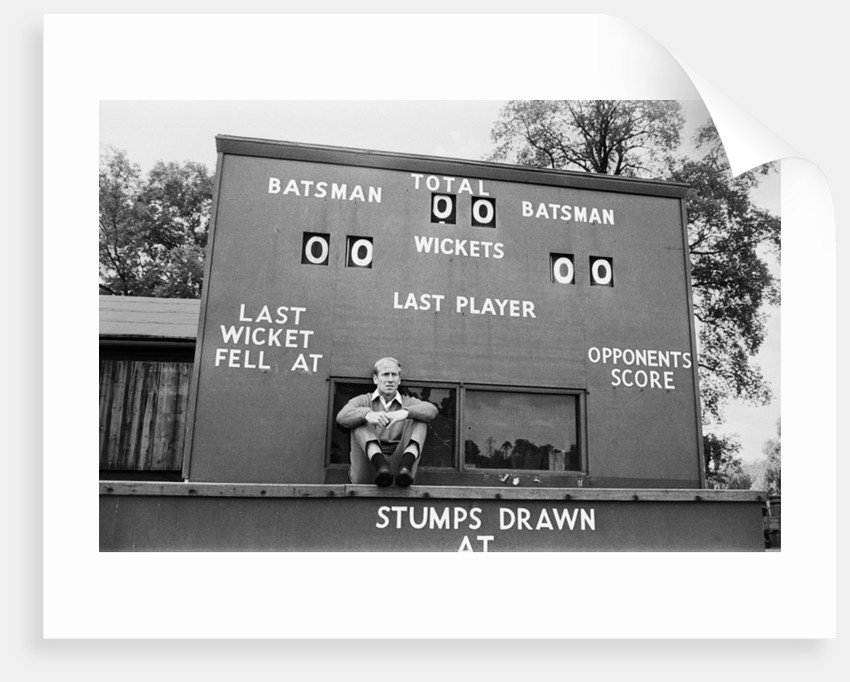Bobby Charlton sits in front of a cricket scoreboard by Anonymous