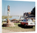 A Triumph hearld car parked next to a signpost at Blakeney by Anonymous