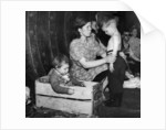 A mother tends to her young son in an underground bomb shelter during an air raid by Staff