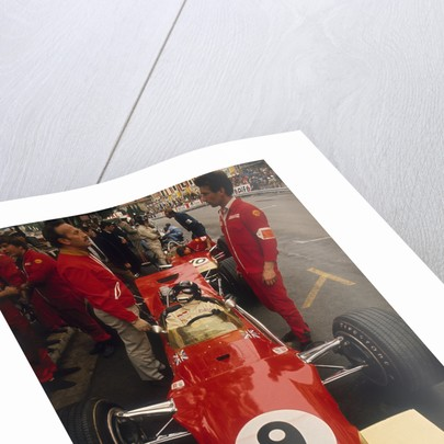 Colin Chapman and a mechanic in discussion over Graham Hill's Lotus by Anonymous