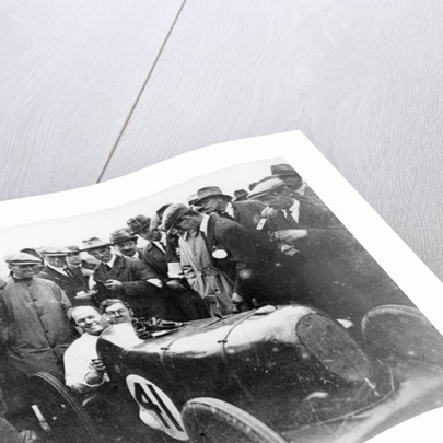 Gordon Taylor in a racing car surrounded by a crowd of men by Unknown