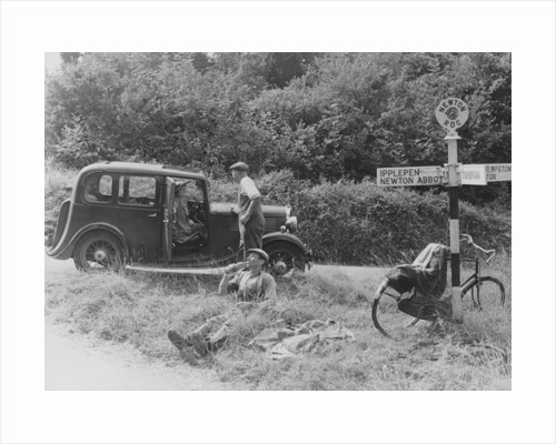 People relaxing by a signpost with a 1935 Standard 10 hp car by Anonymous
