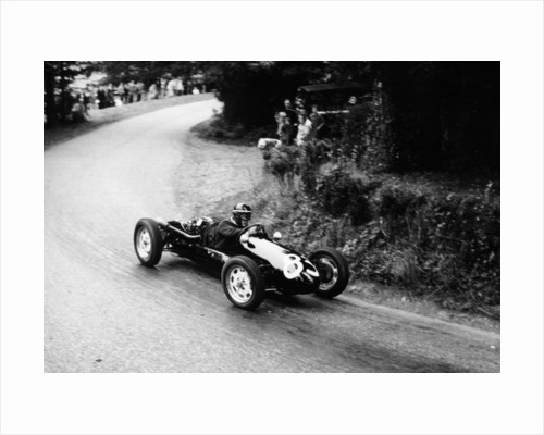 A racing driver speeding round a bend by Anonymous